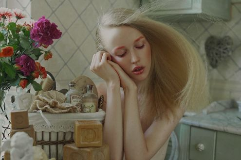 Фото Мечтательная блондинка сидит на кухне у столика с цветами и принадлежностями для мытья, фотограф Marta Bevacqua