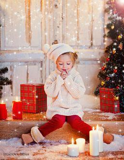 Фото Милая девочка сидит на ступеньке на фоне новогодней елки и подарков, фотограф Филатова Ирина