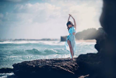 Фото Красивая девушка стоит на берегу моря в прозрачном голубом платье подняла руки над головой