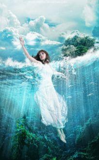Фото Девушка погруженная в море держит сияющую ракушку в руке