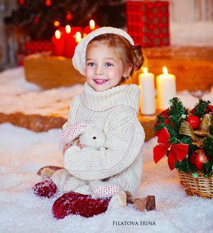 Фото Милая девочка с игрушечным зайцем в руках сидит у новогодней корзины, фотограф Филатова Ирина
