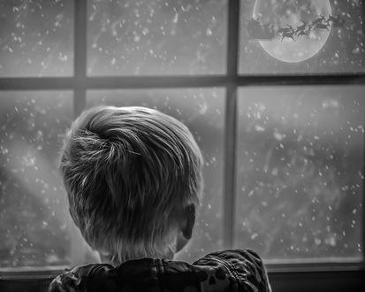 Фото Маленький мальчик смотрит в окно, где на фоне луны проносится упряжка оленей с санями