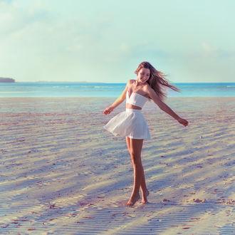 Фото Веселая девушка в белой юбке и топике кружится на песчаном берегу моря, by Sasha Kalis