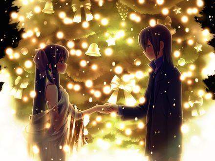 Фото Парень с девушкой, взявшись за руки, стоят на фоне яркой новогодней елки