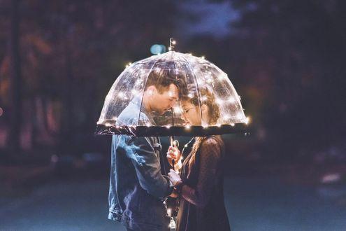 Фото Девушка и парень под прозрачным зонтом, украшенным огоньками, стоят на ночной улице, фотограф Brandon Woelfel