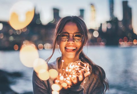 Фото Веселая девушка в очках стоит на фоне реки и города, держа в руках зажженную гирлянду