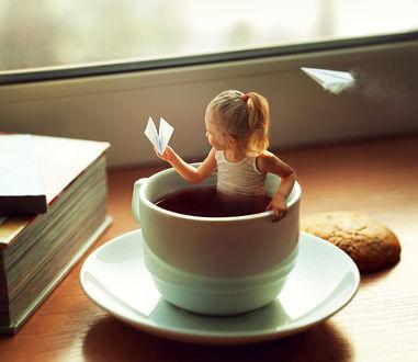 Фото Девочка с бумажным самолетиком сидит в чашке с чаем, фотограф Savenko Yuliya