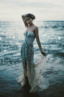 Фото Девушка в блестящем белом платье стоит у морской глади