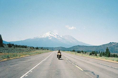 Фото Мотоциклист едет по дороге, позади него виднеется гора на фоне голубого неба