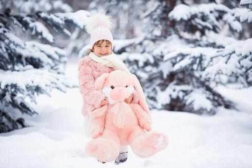 Фото Девочка стоит в зимнем лесу держа в руках игрушку розового зайца
