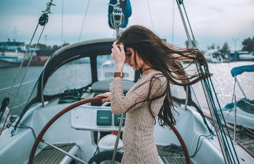 Фото Шатенка с развевающимися длинными волосами, в вязанном платье, стоя на катере держит рукой штурвал, наклонив голову, другой рукой поправляет волосы, на фоне пристани, by Dmitry Rogozhkin