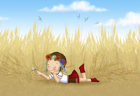 Фото Девочка украинка в венке из цветов со стрекозой на пальце лежит в пшеничном поле