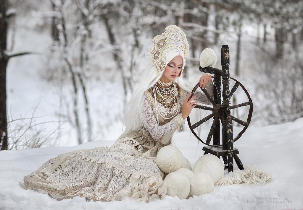 Модель София Глушкова в наряде от дизайнера Дарины Зиминой сидит у прялки на снегу, фотограф Margarita Karev