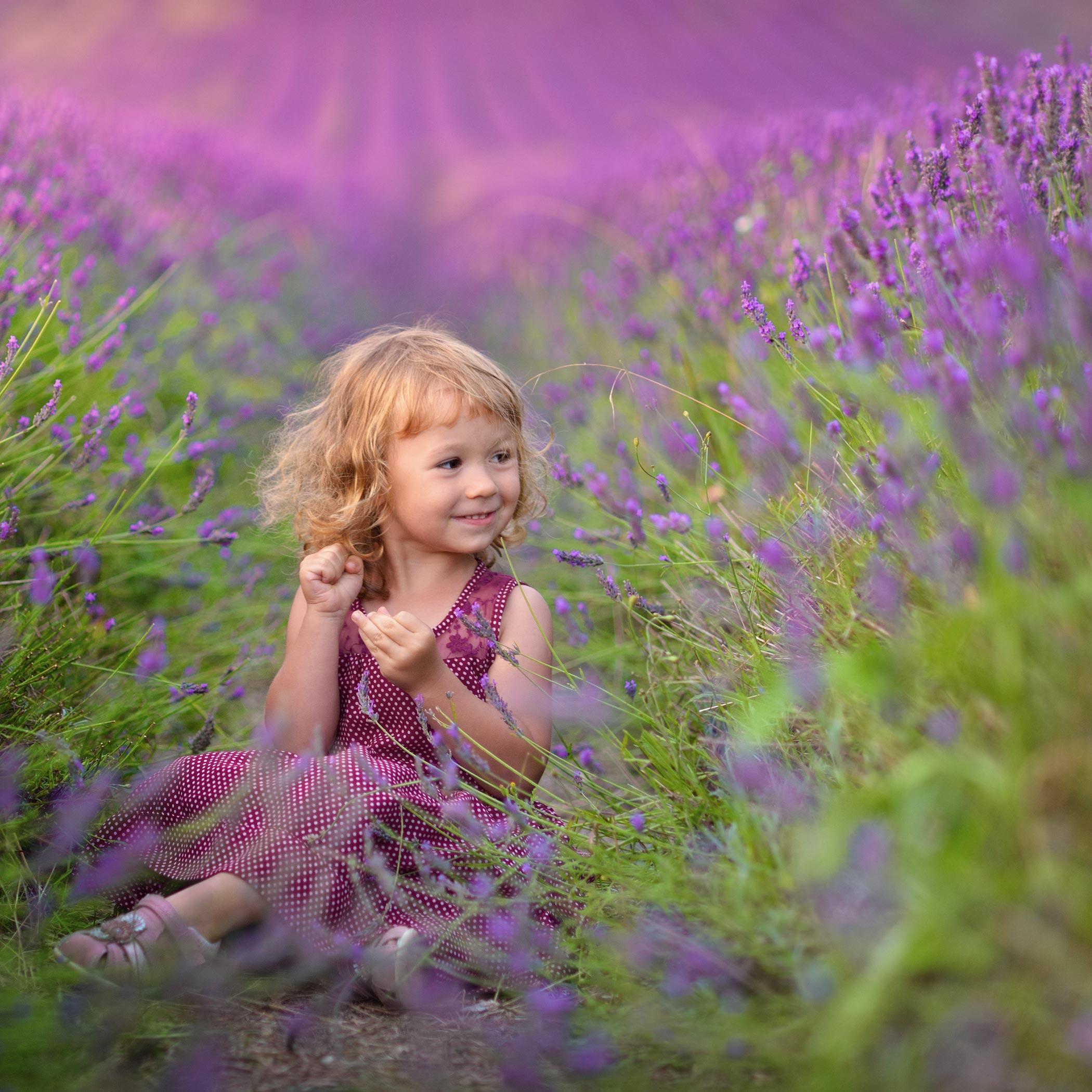 Фото Красивая милая девочка, улыбающаяся, сидит в поле лавандовом, by Dimka Ganeva