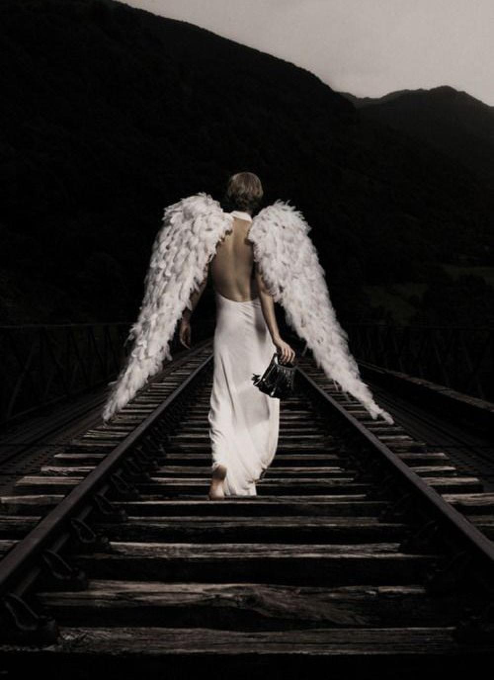 Фото Девушка в белом платье с крыльями ангела уходит по шпалам
