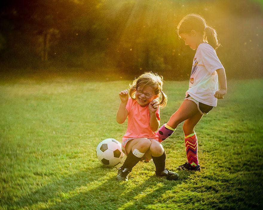 Фото Две девочки на фоне солнечных лучей на зеленой траве играют с футбольным мячом