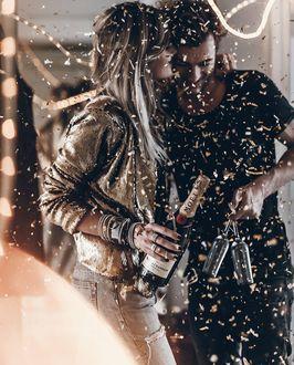 Фото На влюбленных с бокалами и шампанским в руке падают золотые конфетти