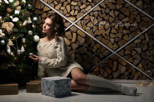 Фото Девушка сидит на полу у новогодней елки