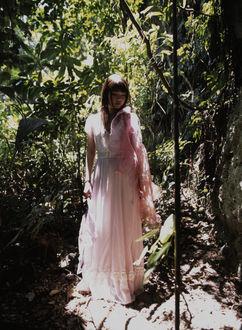 Фото Японская певица Мичишиге Саюми / Michishige Sayumi стоит в тени лесистой местности в розовом платье