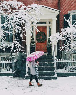 Фото Девушка под розовым зонтом идет рядом с домом, дверь которого украшена рождественским венком