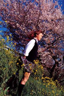 Фото Японская певица Такахаши Ай / Takahashi Ai стоит на склоне холма в школьной форме у сакуры