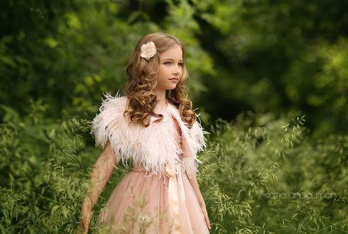 Фото Красивая девочка в нежно-розовом платье с перьями с цветком в волосах стоит в высокой траве, by Katie Andelman