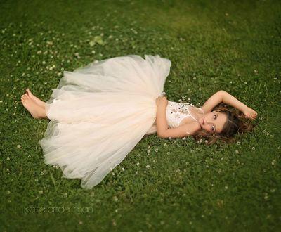 Фото Красивая девочка в пышном белом длинном платье лежит на лугу, by Katie Andelman