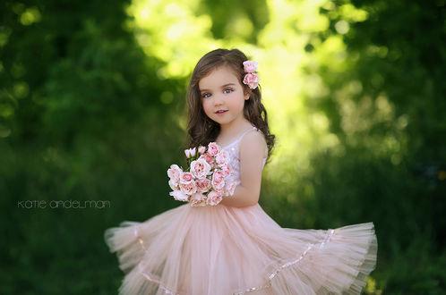Фото Красивая маленькая девочка в легком кремовом платье с розами в волосах и с букетом роз в руках на размытом летнем фоне, by Katie Andelman