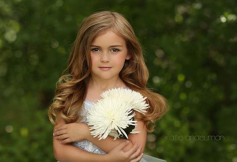 Фото Девочка стоит на летнем размытом фоне держа белые хризантемы, by Katie Andelman