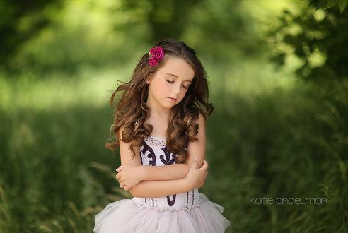 Фото Красивая девочка с розами в волосах, закрыв глаза и скрестив руки на груди, стоит на летнем фоне, by Katie Andelman
