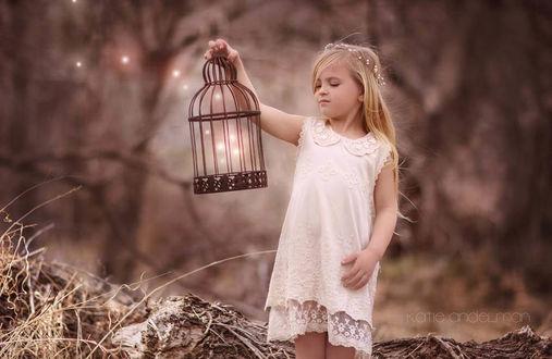 Фото Девочка с венком из бусин на голове держит в руке клетку из которой вылетают светящиеся частички, by Katie Andelman