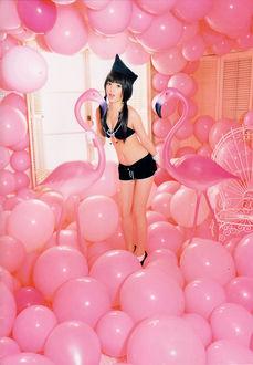Фото Японская певица Мичишиге Саюми / Michishige Sayumi стоит посреди комнаты, заполненной розовыми воздушными шариками, в черном купальнике, держа в руках искусственных фламинго