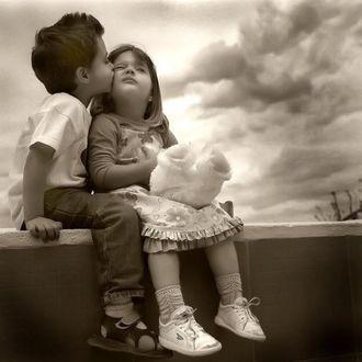 Фото Мальчик целует девочку, девочка, немного смущаясь, принимает поцелуй