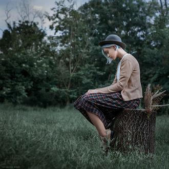 Фото Девушка грустная в шляпке сидит на пне, на фоне природы. Фотограф Дмитрий Бегма