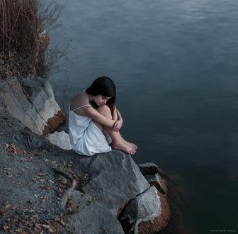 Фото Девушка красивая грустная сидит на камне, на фоне водоема. Фотограф Дмитрий Бегма
