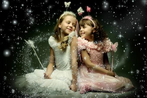 Фото Девочки - феи с волшебными палочками с бабочками, улыбаются друг друг у на новогоднем фоне