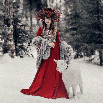 Фото Девушка в красном платье стоит рядом с козой в окружении зимы, фотограф Анна Конофалова