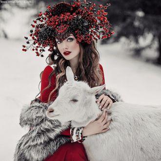 Фото Девушка в красном платье обнимает козу в окружении зимы, фотограф Анна Конофалова