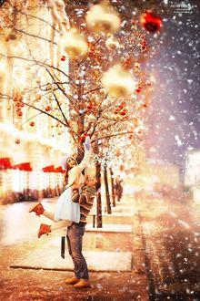 Фото Мужчина держит девушку на руках, которая хочет снять с дерева новогоднюю игрушку, фотограф Алена Горская