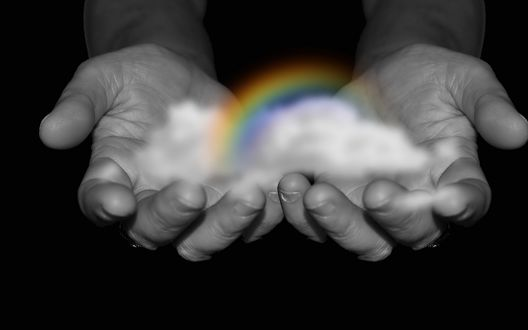 Фото Мужские руки протягивают радугу с облаками на черном фоне