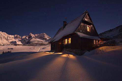 Фото Деревянный домик под зимним ночным небом, фотограф Karol Nienartowicz