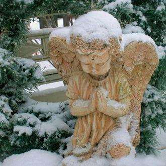 Фото Скульптура ангелочка в снегу среди заснеженных елей
