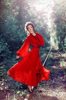 Фото Девушка красивая в красном платье с мечтательным взглядом стоит на рельсах