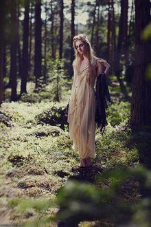 Фото Девушка красивая с закрытыми глазами в платье легком на фоне лесного пейзажа