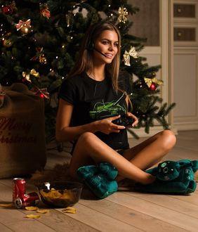 Фото Модель Виктория Одинцова сидит на полу у новогодней елки