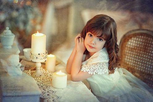Фото Маленькая девочка красивая, сидит в плетенном кресле, облокотившись об стол с горящими свечами. Фотограф Наталья Законова