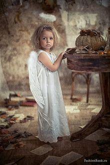 Фото Маленькая белокурая девочка-ангел в окружении разбросанных обгорелых листов, книг и цветов, положила ручки свои нежные на стол, где стоит тыква и связка писем старинных. Фотограф Наталья Законова