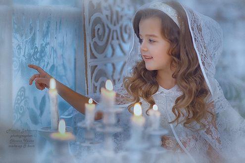 Фото Маленькая девочка в ажурном белом капюшоне невесты на фоне свечей, рисует на замерзшем стекле свои мечты. Фотограф Наталья Законова