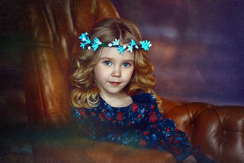 Фото Девочка голубоглазая красивая с венком колокольчиков на голове, сидит в кожаном кресле. Фотограф Наталья Законова