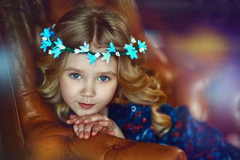 Фото Девочка красивая голубоглазая в венке из колокольчиков, сидит облокотившись на спинку кресла, нежно улыбается. Фотограф Наталья Законова